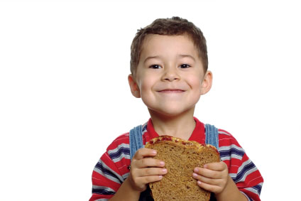 Cute boy ready to eat a peanut butter and jelly sandwich on whole wheat bread